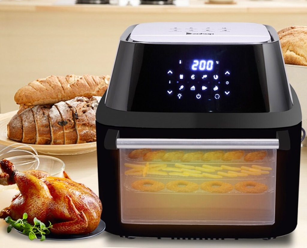Best Air Fryer - black air fryer with three sheets of food inside, with various food on plates surrounding it