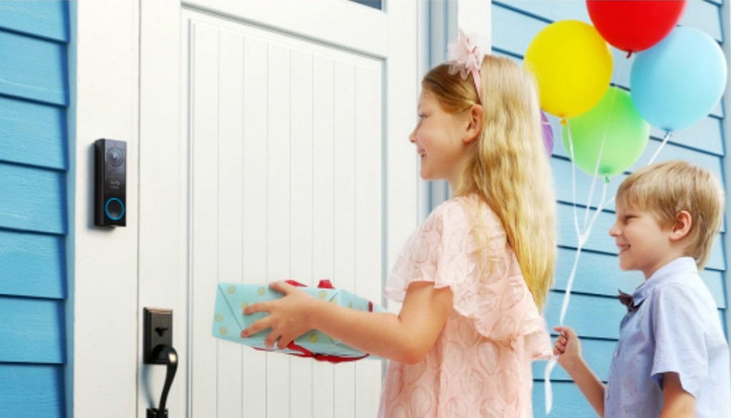 kids standing at front door with video doorbell and holding birthday gift and balloons