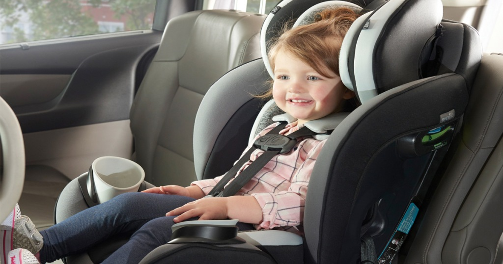 little girl in black and grey car seat inside car