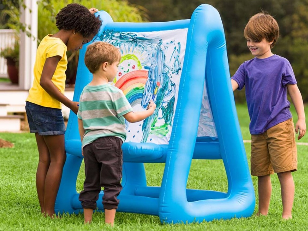 three children using blue inflatable double-sided easel outside