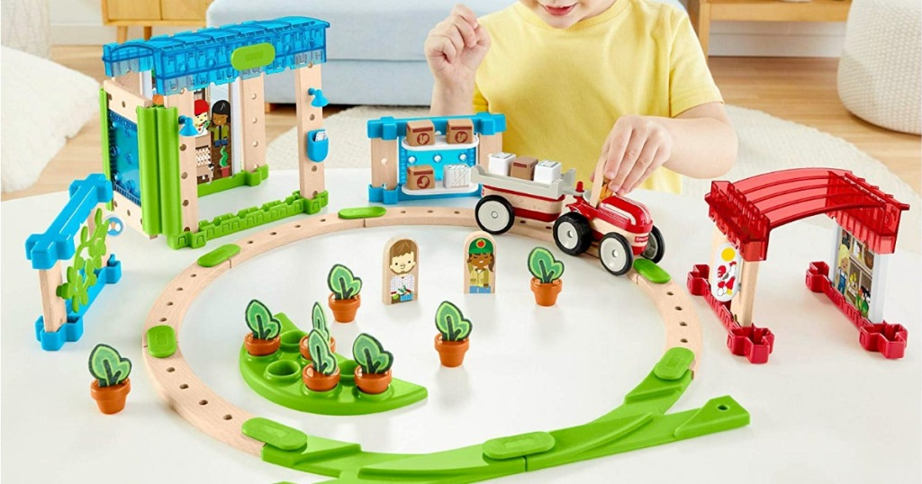 wooden fisher price town set with vehicles on tracks, buildings, and accessories