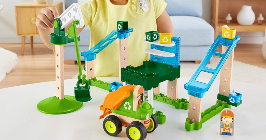 kid playing with Fisher-Price Wonder Makers Design System Lift & Sort Recycling Center