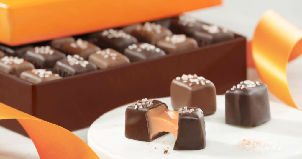 open box of chocolates with three chocolates in front, and one opened showing inside caramel