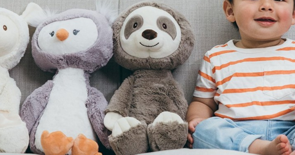 plush sloth sitting next to a baby and other plush animals