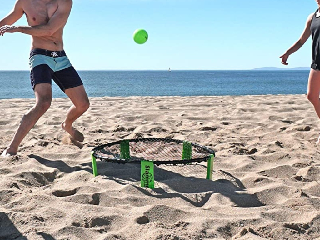 two men playing with tennis ball set on beach