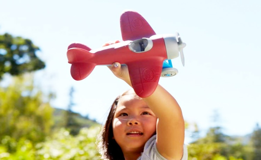 girl holding a red airplane toy in the air