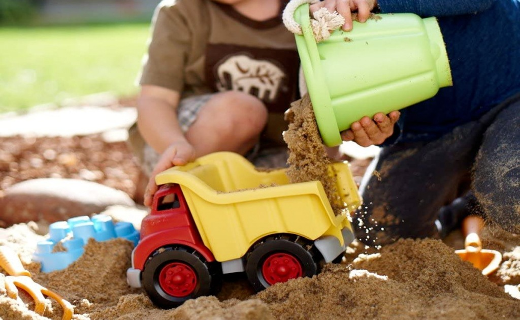 kids pouring sand into a red and yellow dump truck toy in a sand box