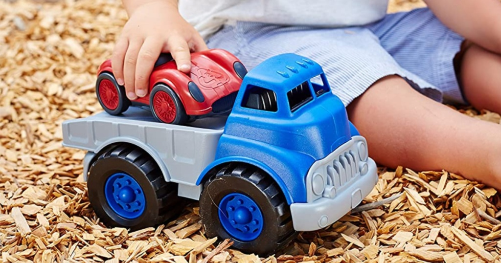 child playing with blue toy truck and red race car in wood chips