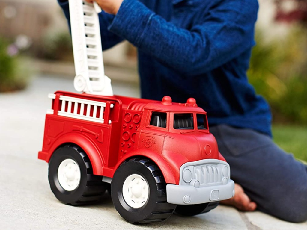 boy in blue shirt playing with red toy fire truck outside