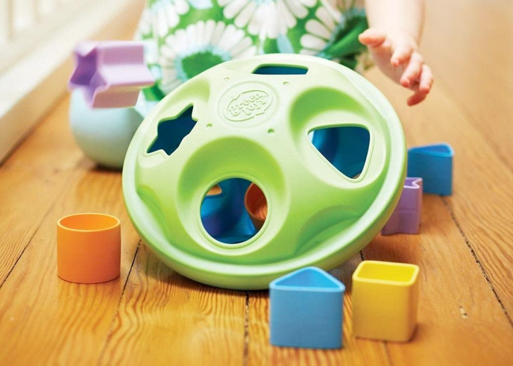 green shape sorting toy on floor with shape pieces laying around it