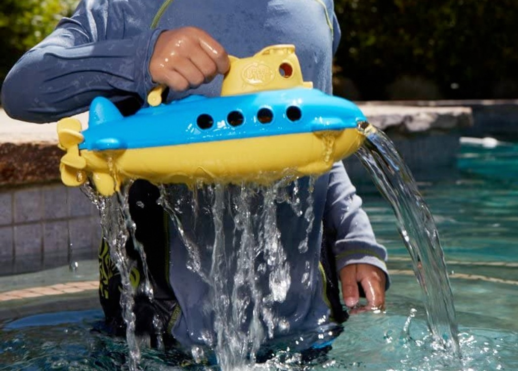 child pulling a blue and yellow submarine toy out of water in a pool