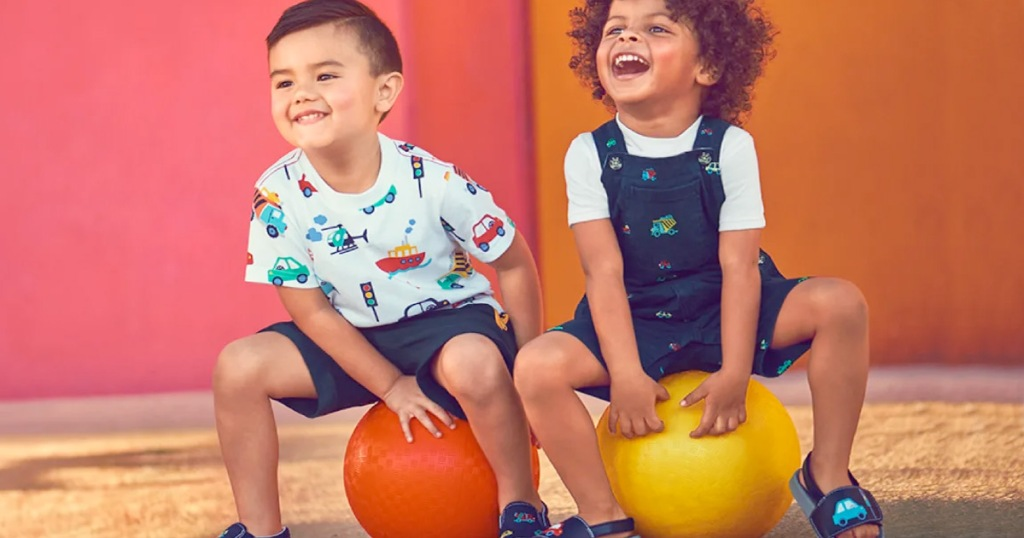 two toddler boys sitting on playground balls wearing vehicle themed clothing