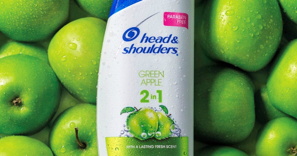 Bottle of 2 in 1 shampoo and conditioner on background of apples