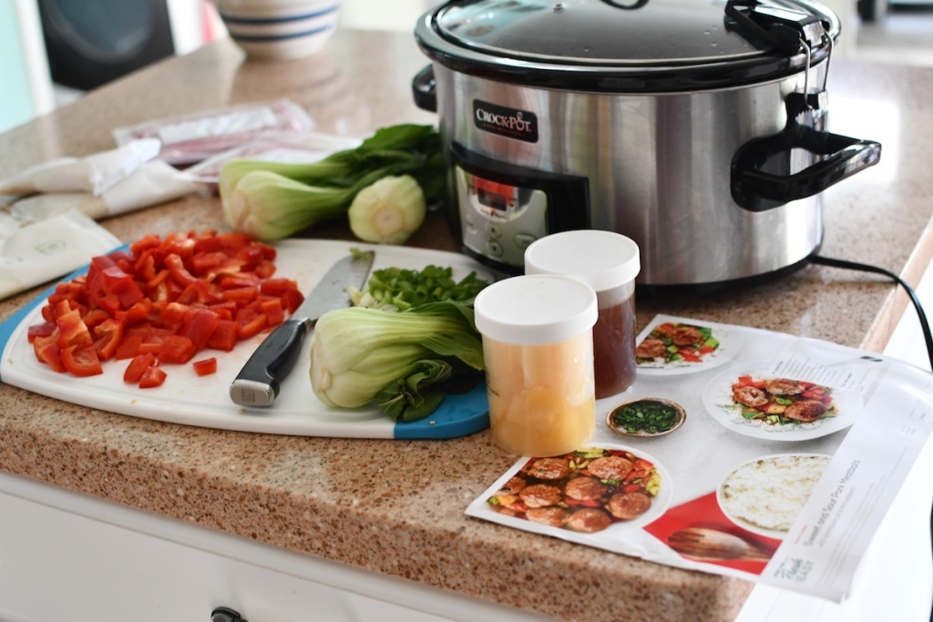 kitchen counter with meal ingredients and slow cooker