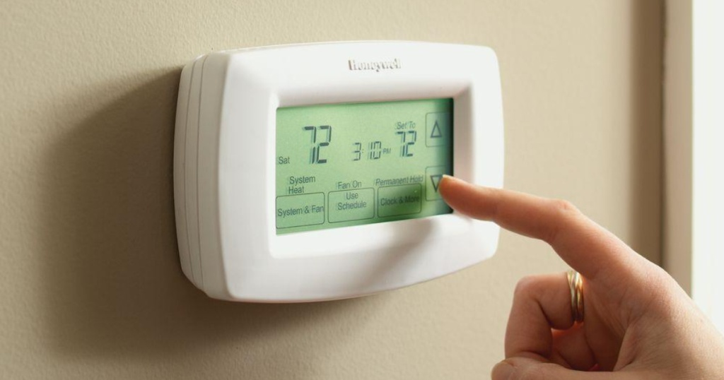 Finger pushing screen on thermostat