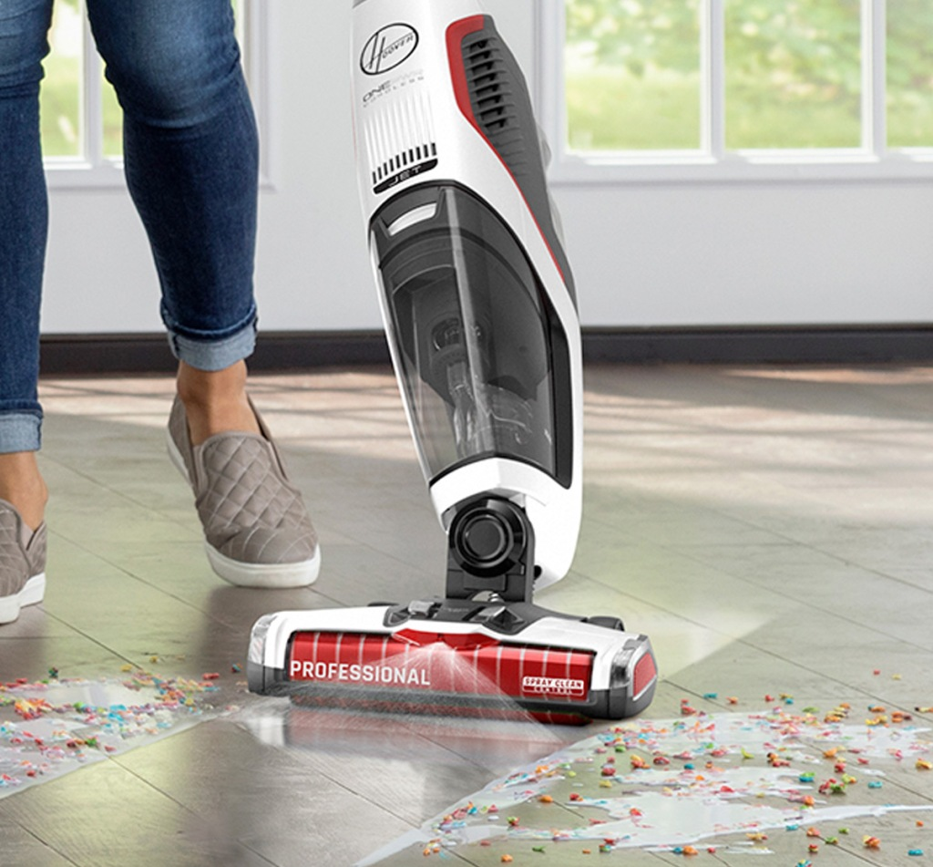 Stick Vacuum Cleaner person using hoover cordless vacuum to clean up spilled cereal on floor and vacuum spraying out cleaning solution in front of it
