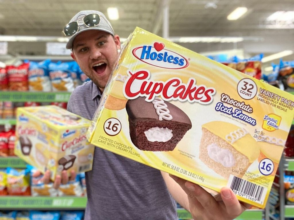 man holding two giant boxes of Hostess cupcakes