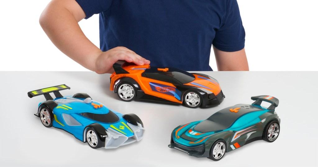 child playing with medium-sized orange car, blue car, and green car
