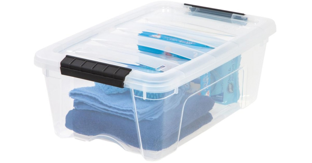 small clear plastic storage container with black latching handles filled with blue colored items inside