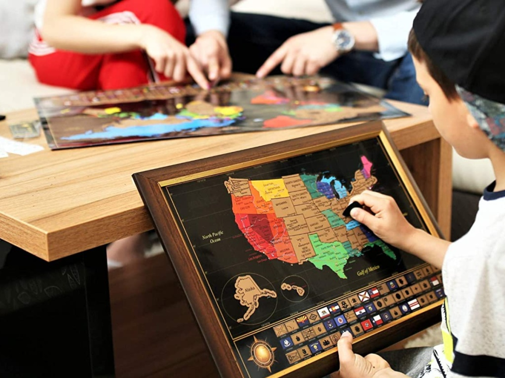 child and parents using scratch off maps on coffee table