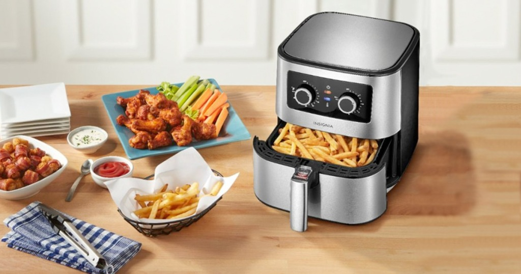 stainless steel and black air fryer on kitchen counter with basket full of fries and plates of fried foods