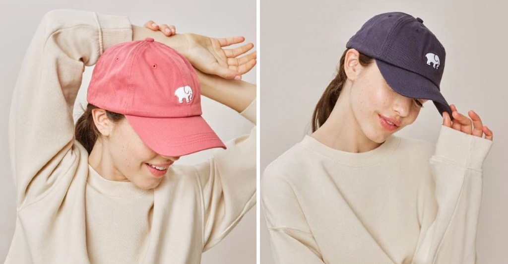 models wearing a light red and navy blue baseball hats with white embroidered elephants on front