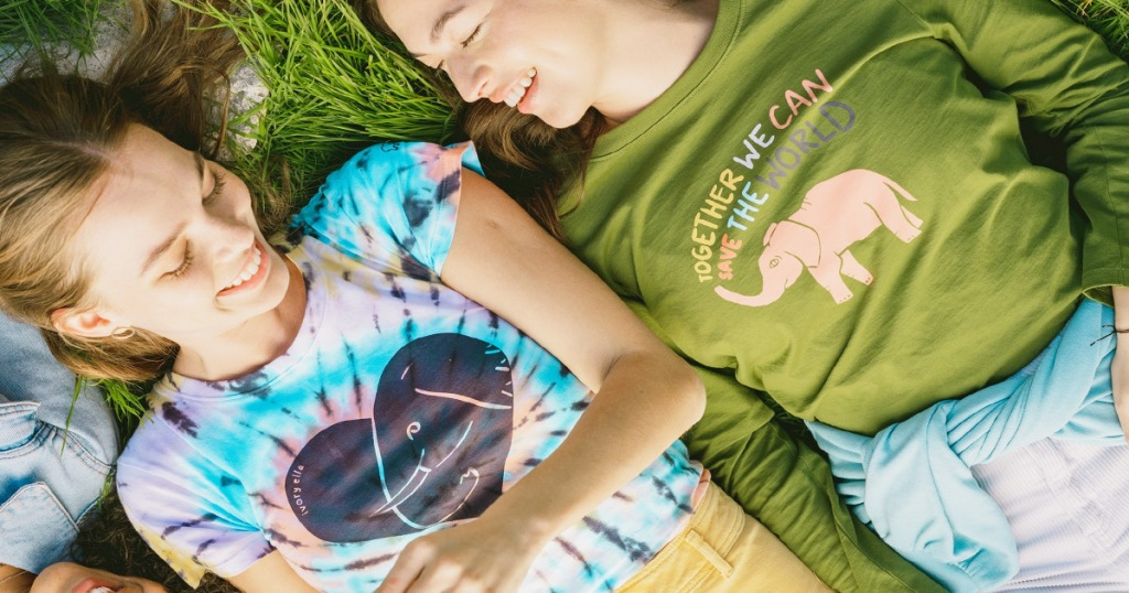 two girls laying in grass wearing elephant graphic tees