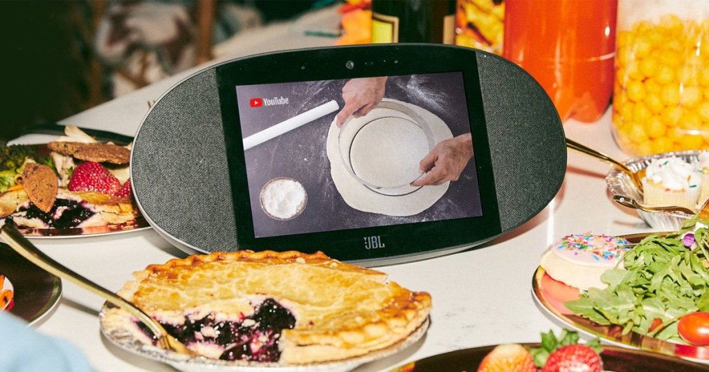 black jbl smart device streaming youtube cooking video sitting on counter surrounded by foods