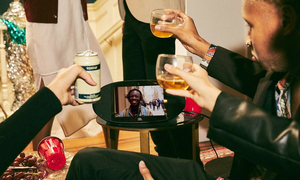 people at party holding up glasses to cheers person video calling on jbl smart device
