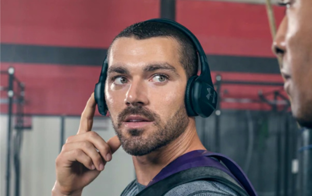 man in gym touching one side of his black headphones