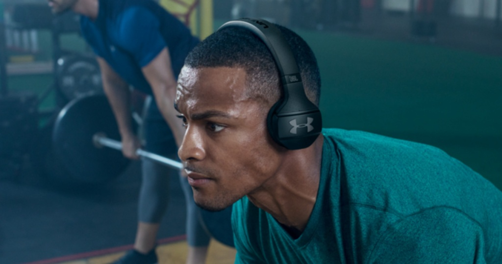man working out in gym with black headphones on