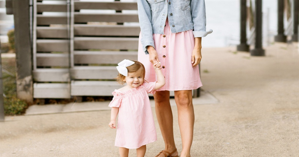 mom with toddler daughter wearing matching pink stripe dresses at beach