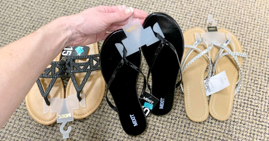 twoman holding up pair of black flip-flops with two other pairs of womens sandals on the floor in the background