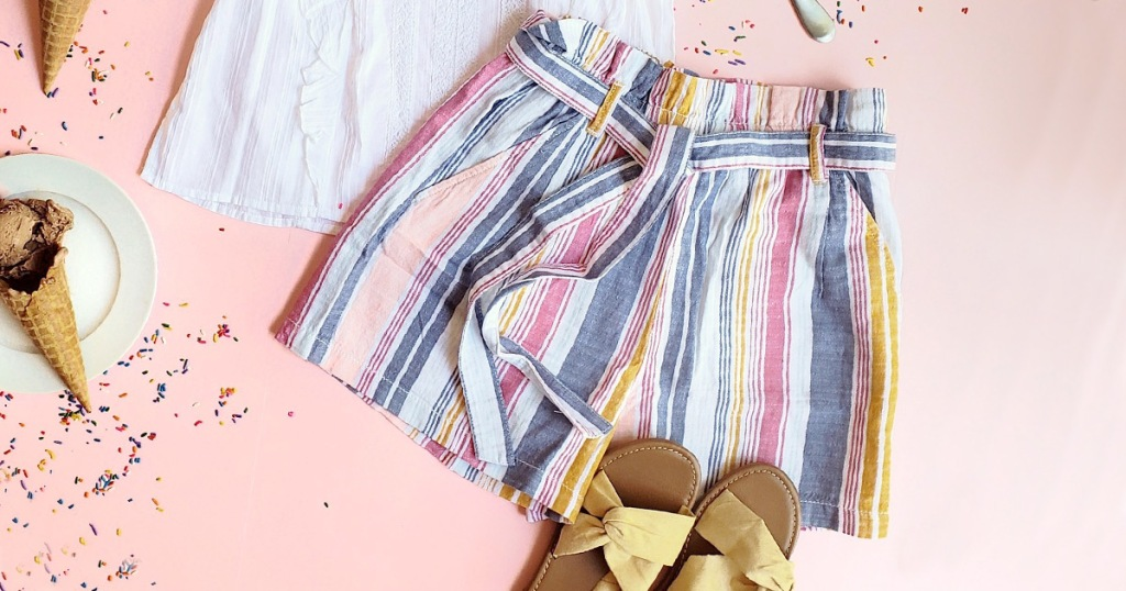 blue, pink, and white striped shorts with tie at waist laying on pink background with white top and yellow sandals