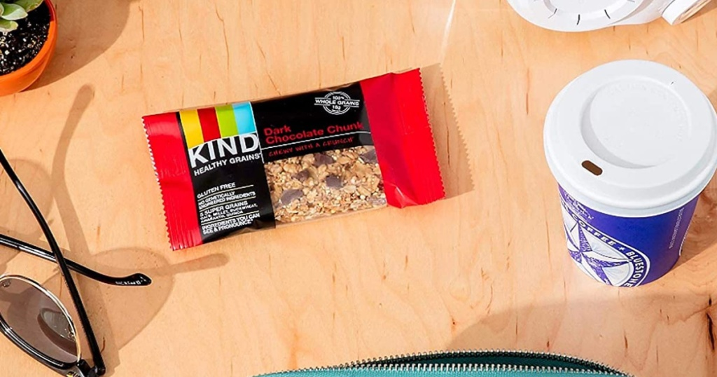 one individual KIND Healthy Grains Bars in Dark Chocolate Chunk bar on table with coffee cup and sunglasses