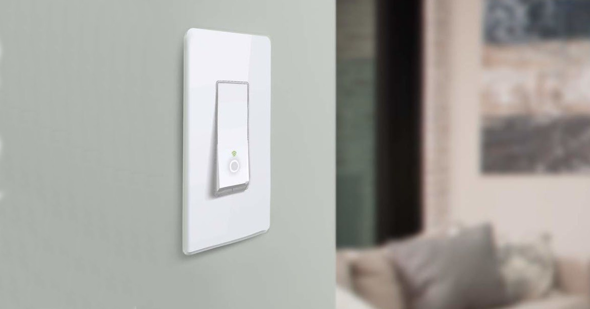 Single Kasa light switch on a green wall next to a living room