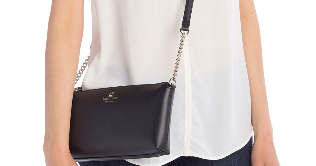 woman in white shirt wearing a black leather kate spade crossbody bag with gold chain