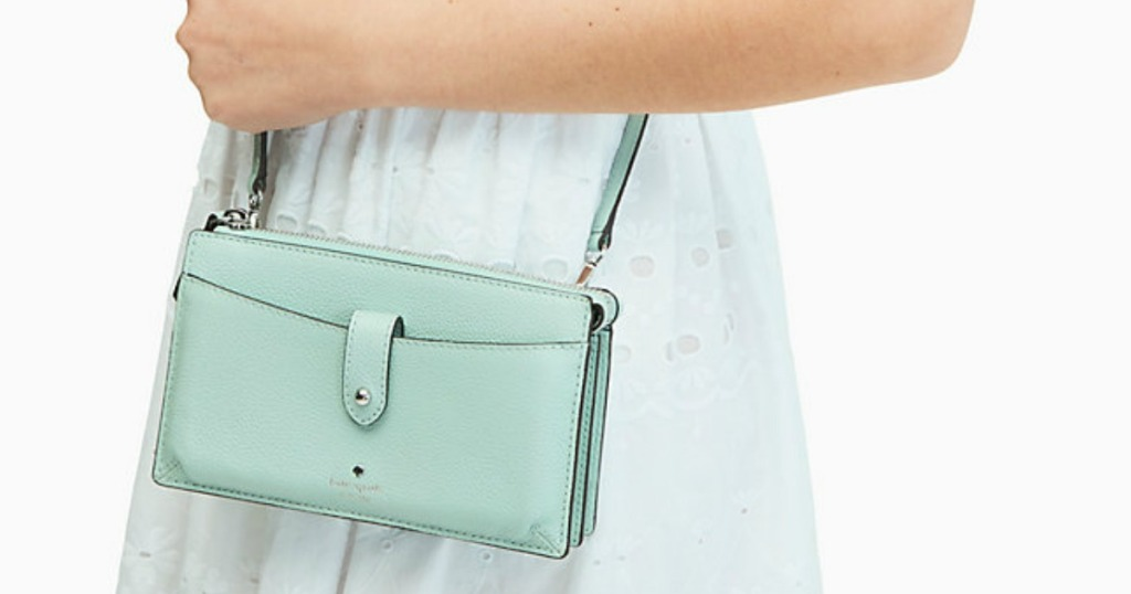 woman holding small mint-colored purse