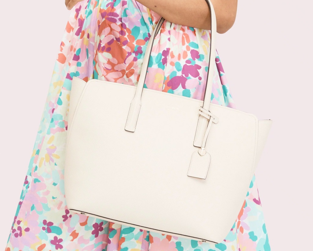 woman in floral dress carrying white leather kate spade tote bag