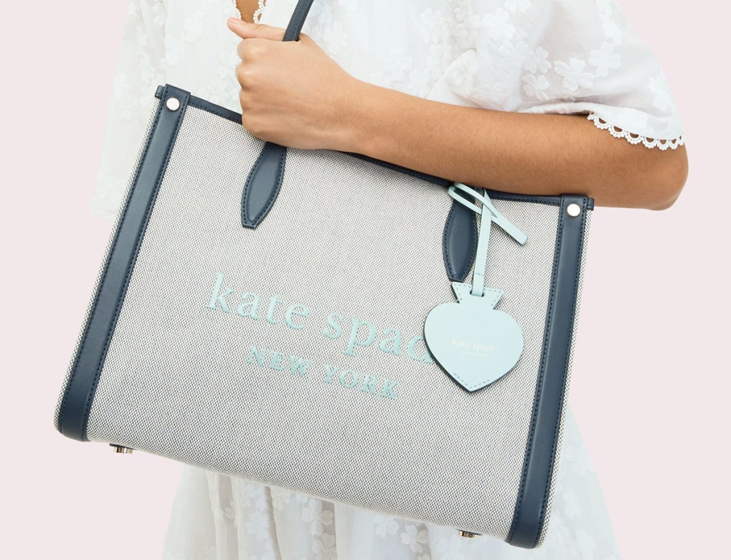 woman carrying a light blue and navy blue colored canvas tote that says kate spade