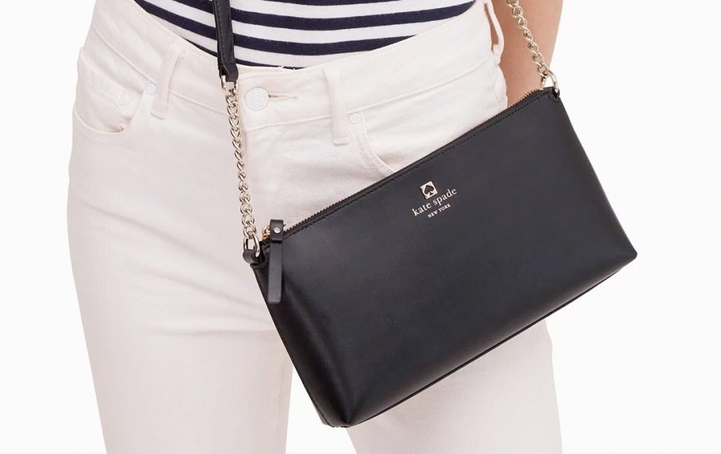 woman in white pants wearing a black leather kate spade crossbody bag with gold chain