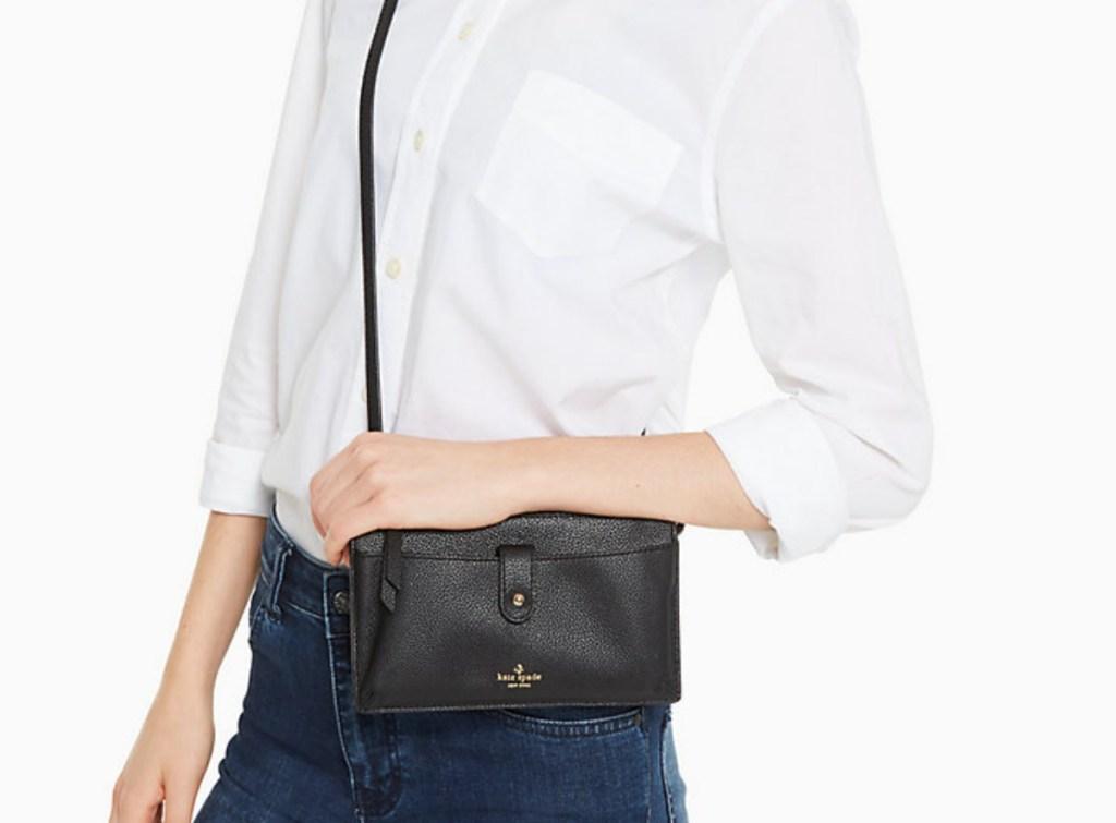 woman holding small black purse