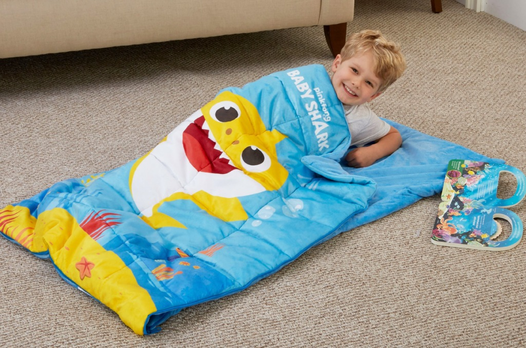 toddler boy laying on floor inside blue baby shark printed sleeping bag with book