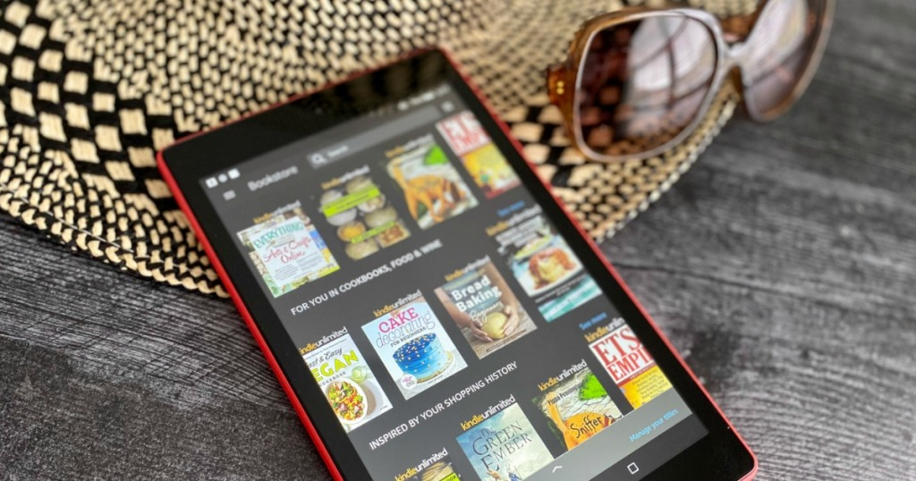 Kindle laying on a hat with books on the kindle