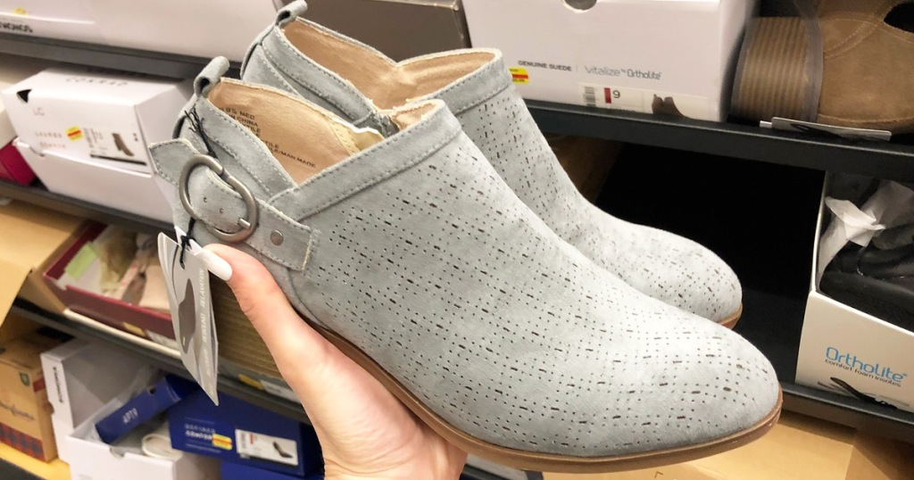 person holding up a pair of light grey ankle booties with cutout design and buckle at ankle