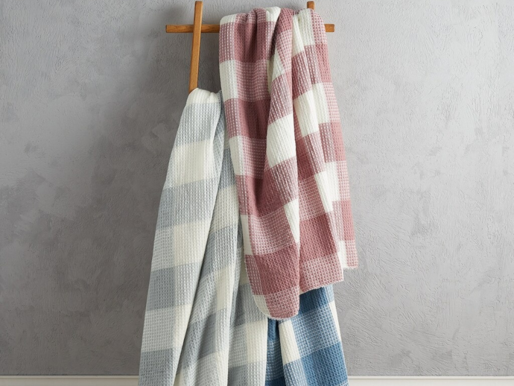 three checkered throws hanging on wooden rack