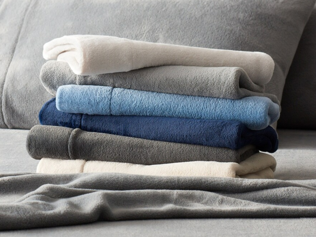variety of colored sheets folded on grey blanket