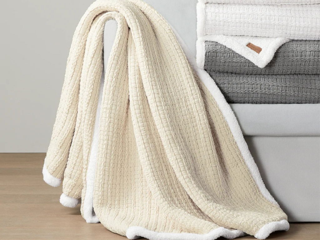 white trimmed cream throw blanket next to stack of white and grey throws