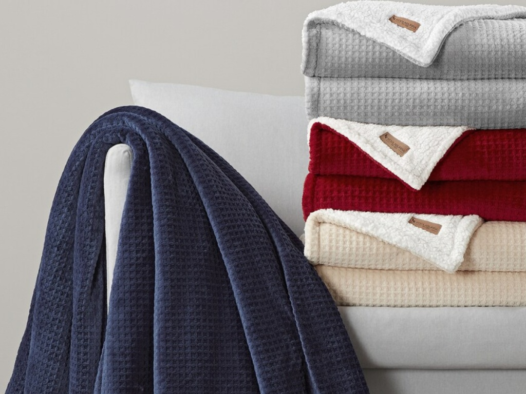 variety of colored throw blankets on gray couch