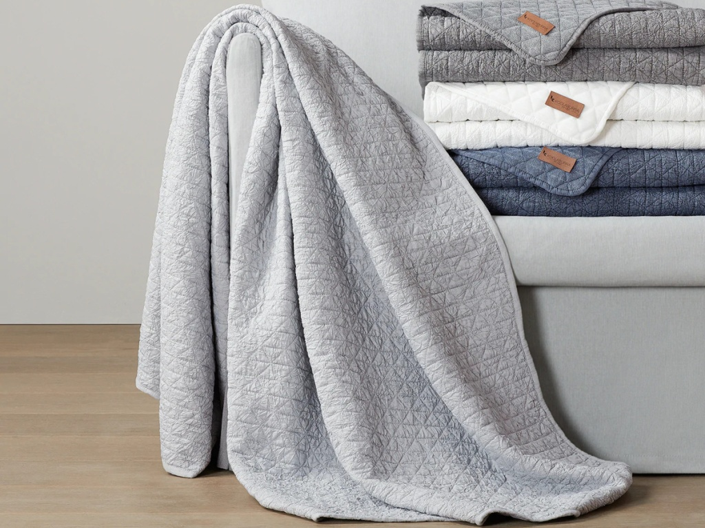 grey throw blanket next to stack of white, blue, and grey throws